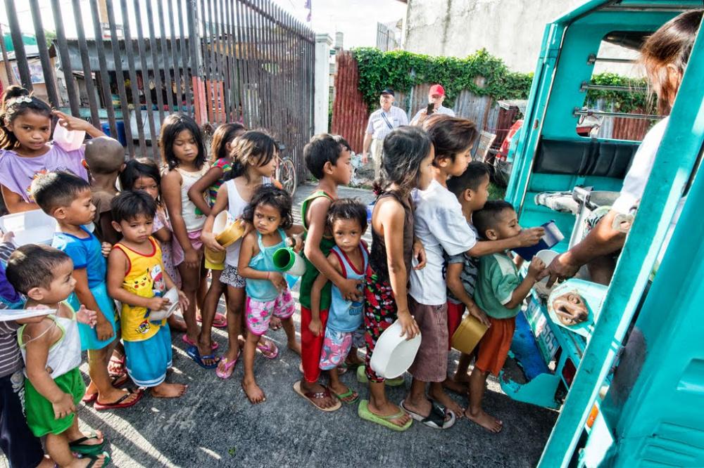 fila di bambini lungo strada davanti ad una baraccopoli per la distribuzione del cibo
